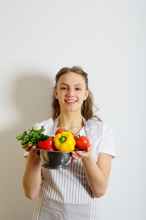 shef: Woman cook and vegetables in a colander Stock Photo