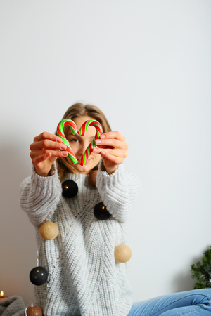 Candy heart from lollipops, woman holding Cristmas lollipops