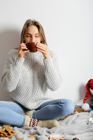 Girl drinking cocoa, sitting with legs crossed and eyes closed. Christmas cosiness. Stock Photo