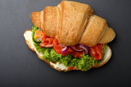 sandwitch: Croissant sandwitch with salmon, food top view slate background