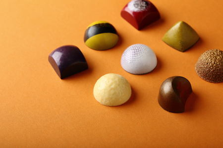 bonbons: Assortment chocolate candy on orange background, food closeup Stock Photo