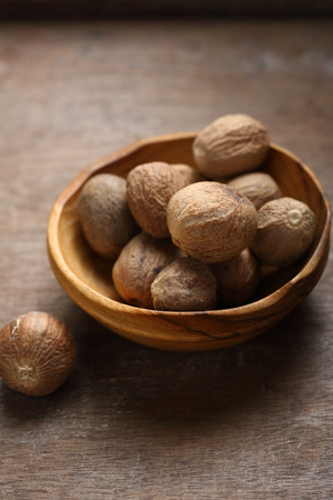 Whole nutmeg in wooden bowl, spice closeup