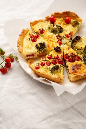Sliced quiche pie on white Foto de archivo - 112472425