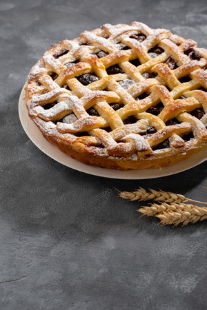 Delicious pie with fruits on gray backdrop