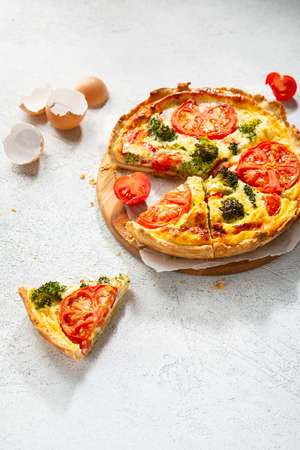 Sliced Quiche lorraine with broccoli and tomato on white surface