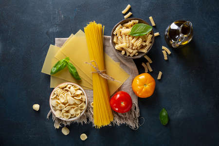 Overhead view of different raw pasta and tomatoes
