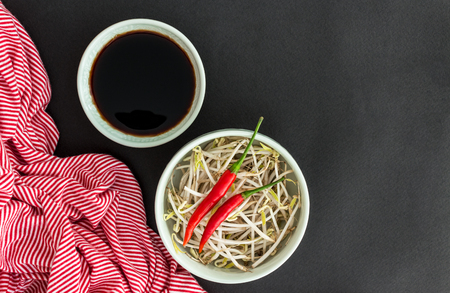 green bean: Red chili peppers on soybean sprouts in green bowl, soy sauce in bowl and a striped towel on black background. Asian food concept.