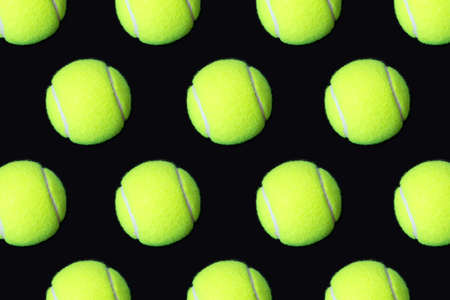Pattern of tennis balls on black background Stock Photo