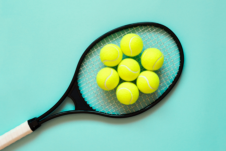Tennis balls on racket. Blue background. Concept sport. Flat lay. Фото со стока
