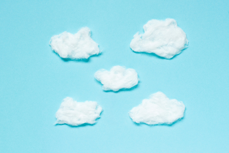 Fluffy Clouds from cotton wool on blue background. Soft texture.