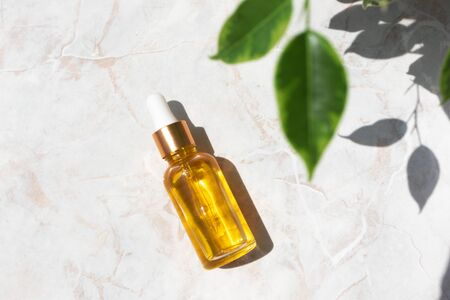 Serum in glass bottle on marble background. Aromatherapy oil, concept of natural cosmetic 免版税图像