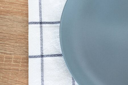 Close-up empty gray plate and white textile napkin on wooden table
