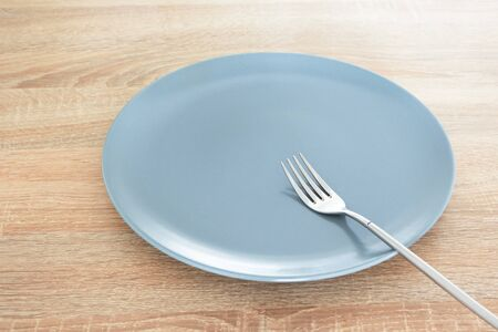 Empty gray plate and silver fork on wooden table Stock Photo