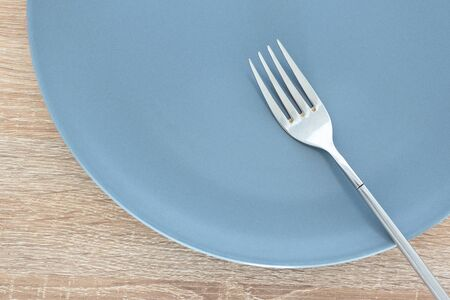Close-up empty gray plate and silver fork on wooden table