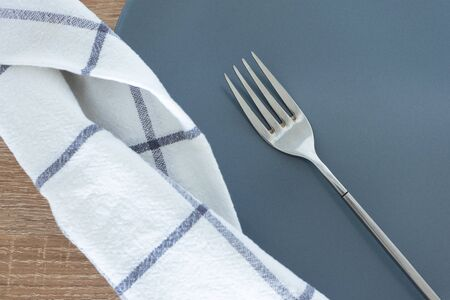 Close-up silver fork; empty gray plate and white textile napkin on wooden table Stock Photo