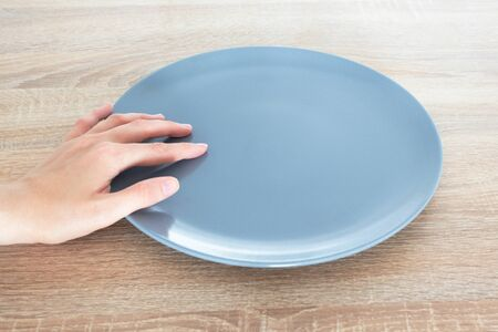Empty gray plate on wooden table and human hand