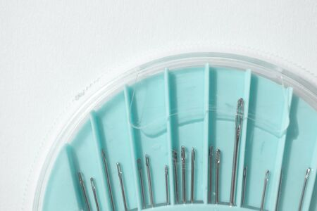 Set of hand-sewing needles in blue round plastic box, close-up. Sewing accessories and tools