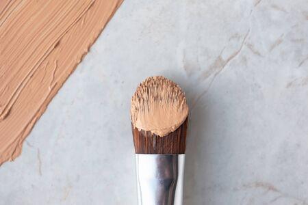 Pędzel do makijażu i kremowy podkład na luksusowym marmurowym tle, powyżej. Profesjonalna okładka kosmetyczna, zbliżenie