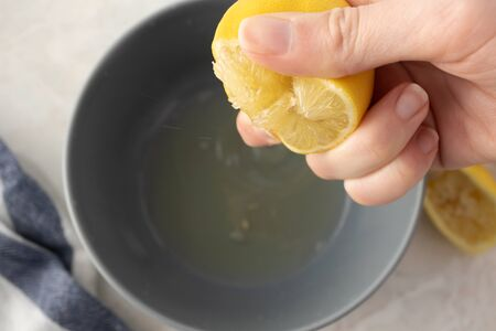Close-up hand squeeze half of lemon over gray bowl with juice on marble table background, above. Selective focus. Make lemonade concept. Healthy drink and food. Natural vitamin C