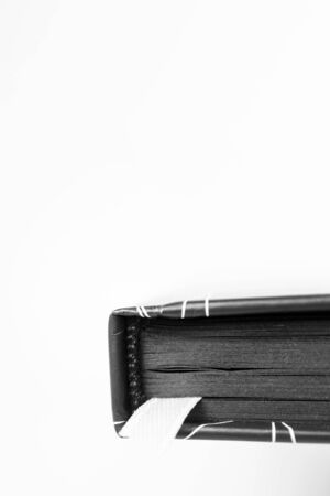 Close-up diary with black paper sheets and white bookmark on white background with copy space, vertical. Isolated