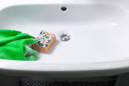 Green rubber gloves and yellow sponge lie on ceramic washbasin. Concept housework, cleaning bathroom