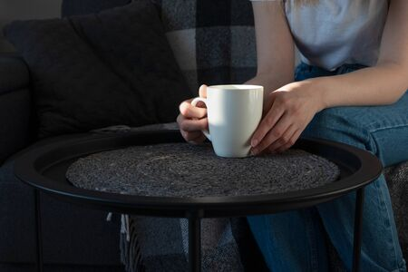 Woman hand holding white cup on coffee table on sofa in sunny day, indoors. Rest in home, lifestyle.