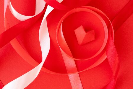 Curly satin ribbons and origami heart on red paper background, close-up. Valentine's day card, poster or invite