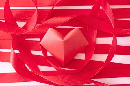 Curly satin ribbons and red origami heart on pink paper background, close-up. Beautiful Valentine's day card Foto de archivo - 140895132
