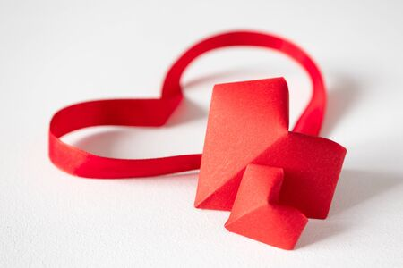 Origami hearts and satin ribbons on white background in front view with copy space. Red paper decor for Valentines day or wedding. Concept beautiful love