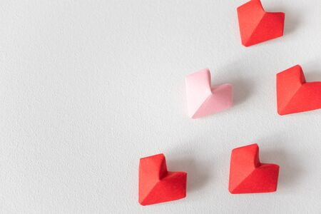Paper hearts diagonals on white background top view. Red and pink origami with copy space. Ð¡ongratulations with Valentine's day or wedding invite, postcard. Concept of difference