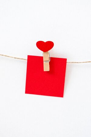 Craft heart wooden mini clothespin and red paper memo on rope twine on white wall, vertical format. Cute postcard for Valentine's day, Wedding party