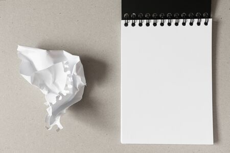 Open notebook with blank white paper sheet and crumpled paper ball on gray background. Horizontal, above. Concept stress, mistakes