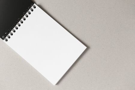 Open notebook with blank white paper sheet and copy space on gray background. Horizontal, above
