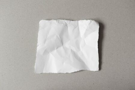 White ripped note, blank of torn crumpled paper on gray background