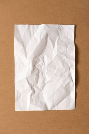 White blank crumpled paper sheet on cardboard background. Top view, vertical. Template for poster. Mockup placard