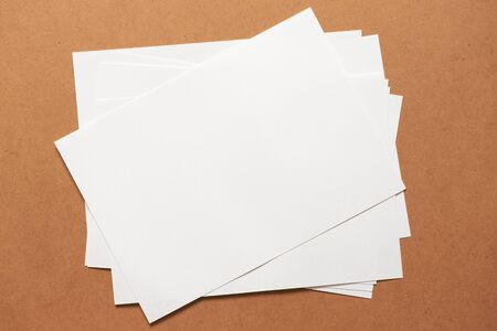 Heap of white empty clean blank paper sheets on cardboard background. Top view, horizontal. Template for poster. Mockup placard