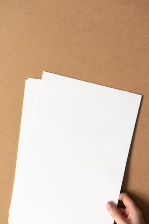 Hand hold white empty clean paper sheets on cardboard background. Top view, vertical. Template for poster. Mockup placard
