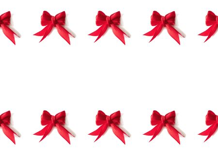 Holiday border from red small textile ribbon bow isolated on white background. Cute frame for gift card, wedding party invite, sale poster or banner, birthday postcard Stock Photo