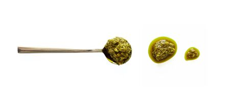 Spoon with pesto and Italian basil sauce splash isolated on white background, top view. Close-up seasoning and dip Foto de archivo