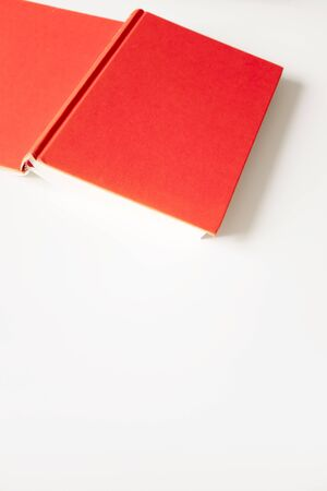 Open book in red cover with selective focus and copy space on white background, top view. Concept education, learning and studying, vertical