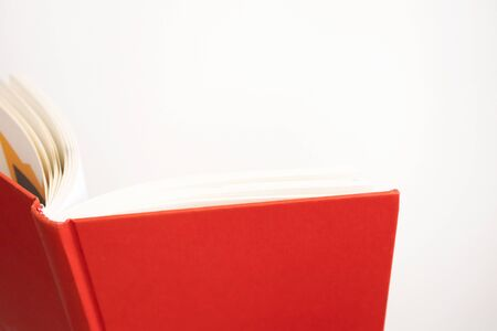 Opened book in red cover with selective focus on white background and copy space. Concept education, learning and studying