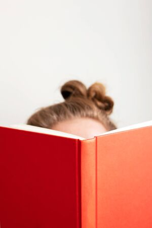 Young woman reads book. Selective focus on red book. Concept education, learning and studying at home