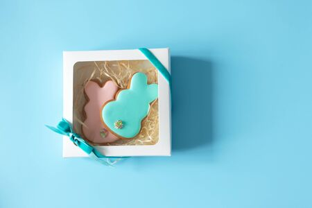Funny glazed cookies rabbit shape in gift box on blue background with copy space. Easter food tradition