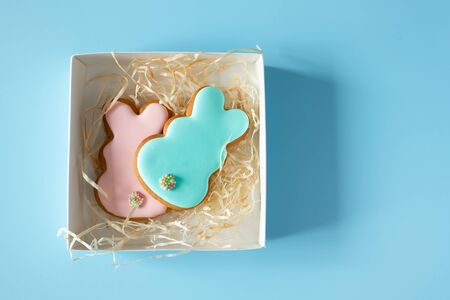 Homemade Easter cookies in gift box on blue background with copy space. Easter food tradition Foto de archivo