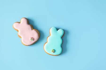 Homemade Easter cookies rabbit shape on blue background with copy space. Easter food tradition