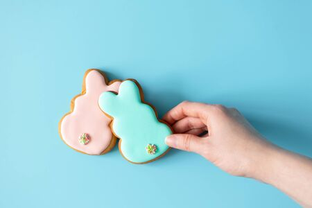 Woman takink Easter cookies rabbit shape on blue background with copy space, top view
