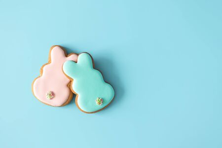 Two homemade Easter glazed cookies rabbit shape on blue background with copy space. Easter food tradition, top view