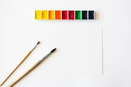 Blank empty paper sheet, paintbrushes and colorful watercolor on white background. Creative workspace, top view