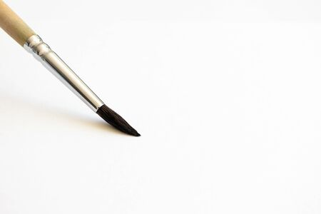 Close-up paintbrush on white watercolor paper with selective focus and copy space, horizontal. Hobby and art tool
