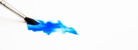 Blue watercolor stain texture and paintbrush on white paper with selective focus and copy space. Hobby and art horizontal banner format